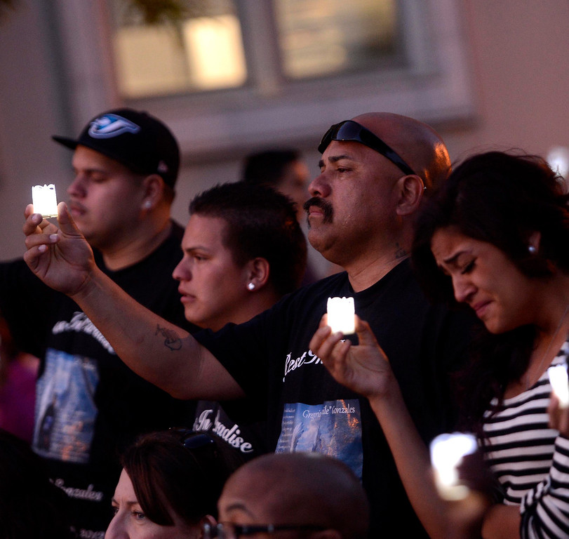 . James Gonzales and niece Marisa, 19, commemorate the life of  homicide victim Gregorio Gonzales, 19, during the annual Victims Candlelight Vigil at the police station in San Bernardino April 23, 2013.   GABRIEL LUIS ACOSTA/STAFF PHOTOGRAPHER.