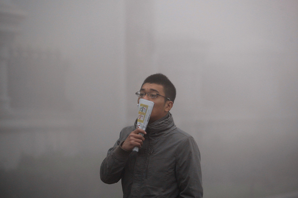 . A Chinese man covers his nose and mouth as he walks on the street during a day of heavy pollution in Harbin in northeast China\'s Heilongjiang province Monday Oct. 21, 2013.  Visibility shrank to less than half a football field and small-particle pollution soared to a record 40 times higher than an international safety standard in the northern Chinese city as the region entered its high-smog season. (AP Photo)