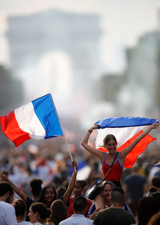 . People celebrate with French flags on the Champs Elysees avenue after France won the soccer World Cup final match between France and Croatia, Sunday, July 15, 2018 in Paris. France won its second World Cup title by beating Croatia 4-2 . (AP Photo/Francois Mori)