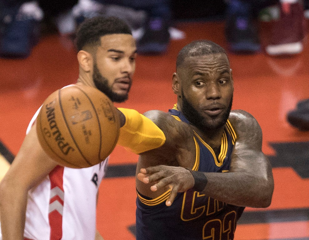 . Cleveland Cavaliers\' LeBron James, right, passes off the ball under the basket as Toronto Raptors guard Cory Joseph (6) looks on during the first half of Game 3 of an NBA basketball second-round playoff series in Toronto on Friday, May 5, 2017. (Fred Thornhill/The Canadian Press via AP)