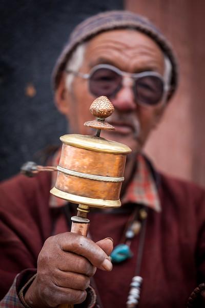Tibetan Buddhist man spinning hand prayer wheel. Lamayuru gompa, Ladakh, India