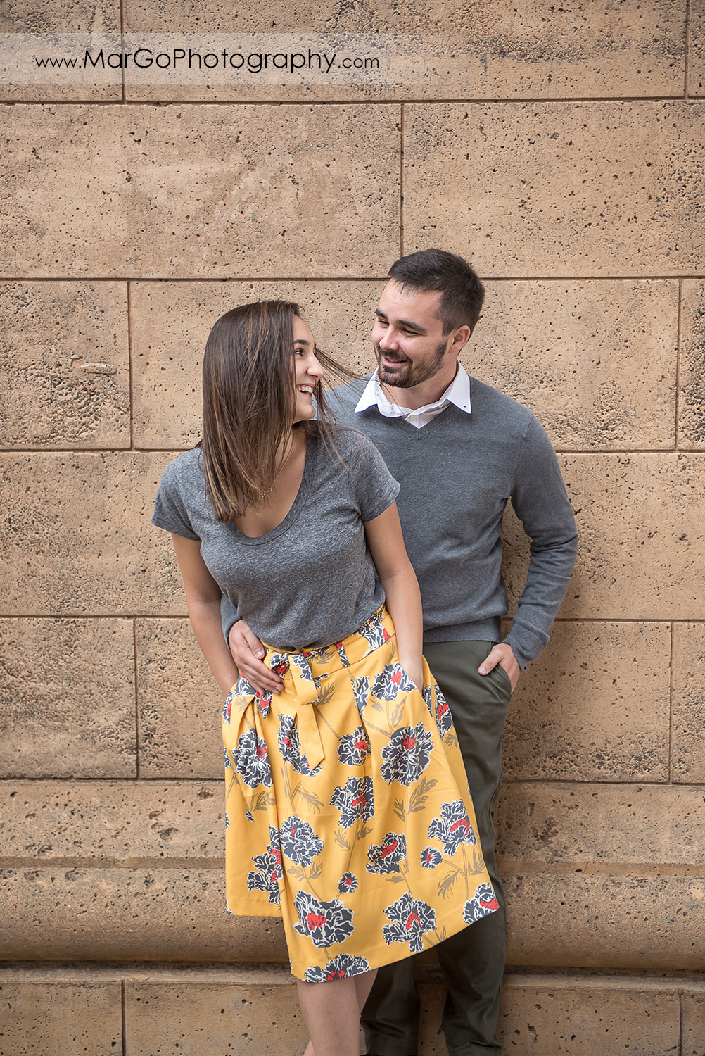 engagement session at Palace of Fine Arts in San Francisco - couple laughing on the stone wall