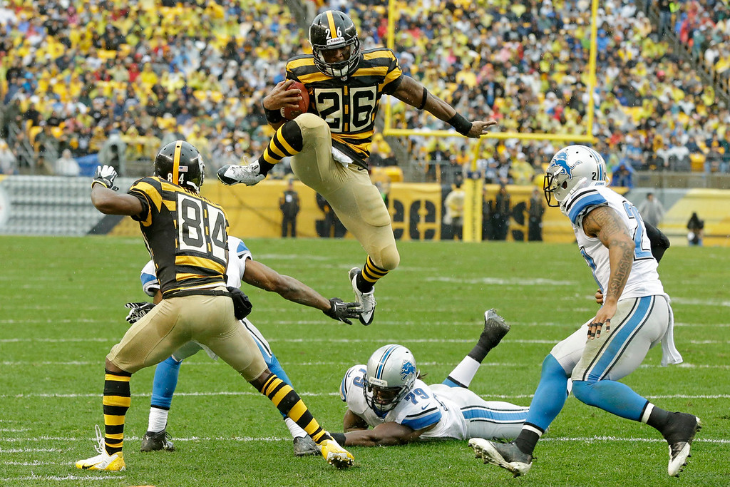 . Pittsburgh Steelers running back Le\'Veon Bell (26) leaps for more yardage as he tries to evade Detroit Lions strong safety Glover Quin (27) and the defense in the first half of an NFL football game in Pittsburgh, Sunday, Nov. 17, 2013. (AP Photo/Gene J. Puskar)