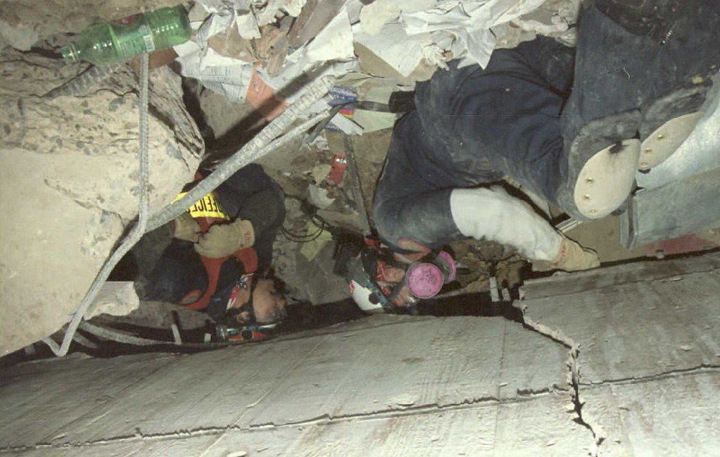 . Rescue workers dig, 29 April 1995, through the ruble of the Federal Building in Oklahoma City looking for survivors of the 19 April bombing. Work was halted during 29 April because of falling debris that was a danger to the rescuers.            Green bottle in upper right of vertical photo.  Roman BAS/AFP/Getty Images)