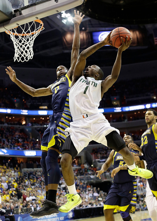 . Miami guard Durand Scott (1) shoots over Marquette forward Jamil Wilson (0) during the second half of an East Regional semifinal in the NCAA college basketball tournament, Thursday, March 28, 2013, in Washington. Marquette won 71-61. (AP Photo/Pablo Martinez Monsivais)