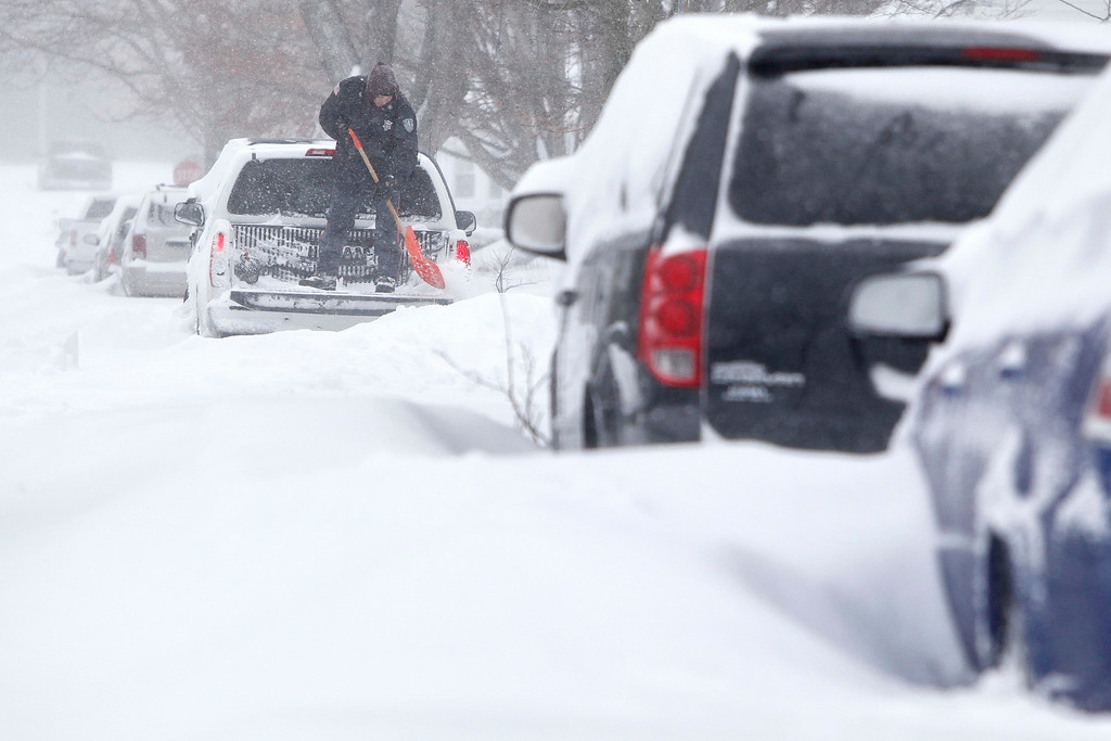 . Peter Nieuwenhuizen digs his truck out as he prepares to drive to work in Norfolk, Mass., on Tuesday, Jan. 27, 2015.  Massachusetts was pounded by snow and lashed by strong winds early Tuesday as bands of heavy snow left some towns including Sandwich on Cape Cod and Oxford in central Massachusetts reporting more than 18 inches of snow.  (AP Photo/Standard Times, Peter Pereira)