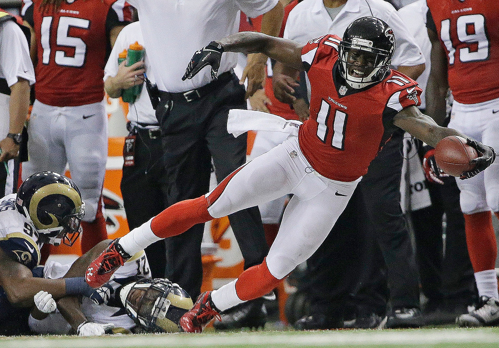 . Atlanta Falcons wide receiver Julio Jones (11) stretches after making a catch against St. Louis Rams cornerback Janoris Jenkins (21) and St. Louis Rams defensive end Eugene Sims (97) during the second half of an NFL football game, Sunday, Sept. 15, 2013, in Atlanta. (AP Photo/David Goldman)
