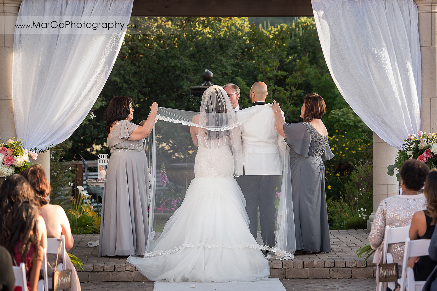 sponsors draping the veil over bride and groom during wedding ceremony at Sunol's Casa Bella