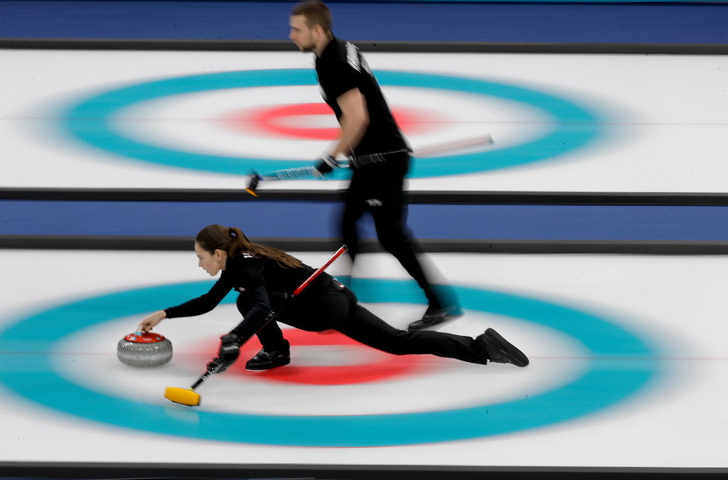 . Russian athlete Anastasia Bryzgalova, below, throws the stone as teammate Aleksandr Krushelnitckii looks on during the mixed doubles semi-final curling match against Switzerland Jenny Perret and Martin Rios at the 2018 Winter Olympics in Gangneung, South Korea, Monday, Feb. 12, 2018. (AP Photo/Natacha Pisarenko)