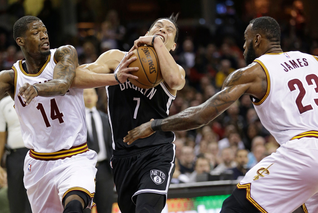 . Brooklyn Nets\' Jeremy Lin, center, drives between Cleveland Cavaliers\' DeAndre Liggins, left, and LeBron James in the first half of an NBA basketball game, Friday, Dec. 23, 2016, in Cleveland. (AP Photo/Tony Dejak)