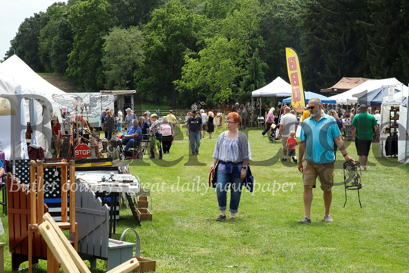 Art-goers and residents walk from booth to booth enjoying food, music and the works of artists and craftsman at Whispering Pines Festival in the woods Saturday. Seb Foltz/ Butler Eagle