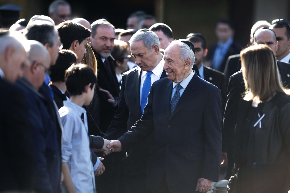 . Israel\'s President Shimon Peres (C-R) and Prime Minister Benjamin Netanyahu (C) offer their condolences to the family of late premier Ariel Sharon as Foreign Minister Avigdor Lieberman looks on (C-L) during a state memorial service at the Knesset (Israeli Parliament) in Jerusalem on January 13, 2014, as Israel was burying one of its most skilled but controversial political and military leaders who was hailed internationally for his tireless dedication to the Jewish state. Sharon died at the age of 85 following eight years in a coma. (MENAHEM KAHANA/AFP/Getty Images)