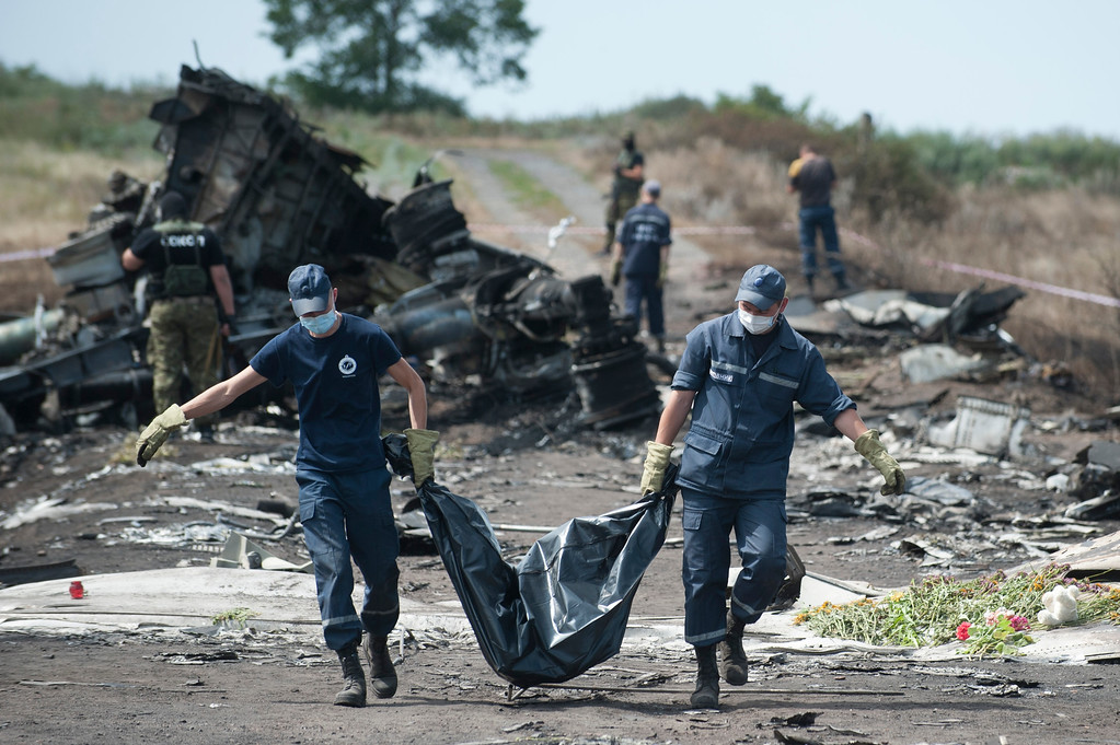 . Ukrainian Emergency workers carry a victim\'s body in a body bag as pro-Russian fighters stand in guard at the crash site of Malaysia Airlines Flight 17 near the village of Hrabove, eastern Ukraine, Sunday, July 20, 2014. Rebels in eastern Ukraine took control Sunday of the bodies recovered from downed Malaysia Airlines Flight 17, and the U.S. and European leaders demanded that Russian President Vladimir Putin make sure rebels give international investigators full access to the crash site. (AP Photo/Evgeniy Maloletka)