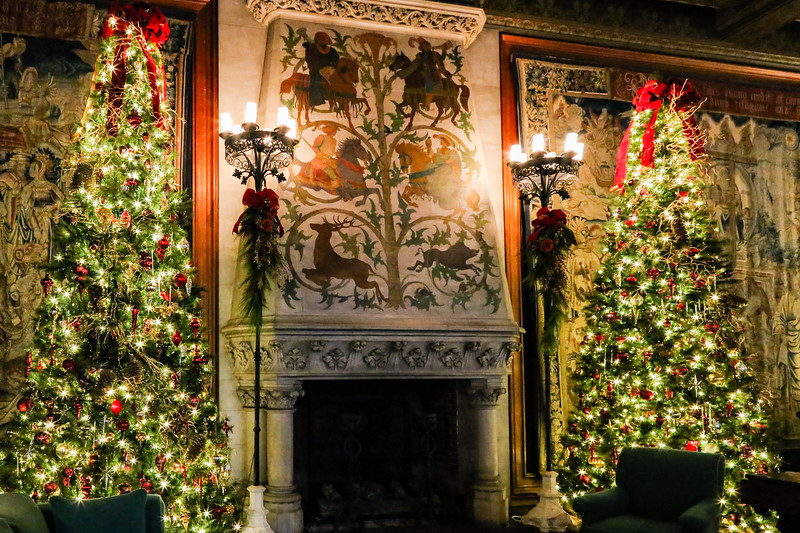 Two elaborately decorated Christmas trees on either side of an antique mantle.