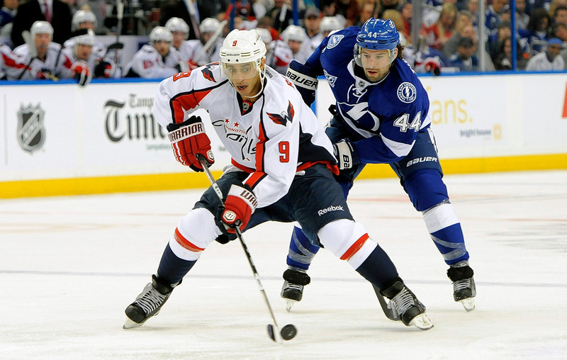 . Washington Capitals center Mike Ribeiro, left, controls the puck against Tampa Bay Lightning center Nate Thompson during the first period of an NHL hockey game Saturday, Jan. 19, 2013, in Tampa, Fla. (AP Photo/Brian Blanco)