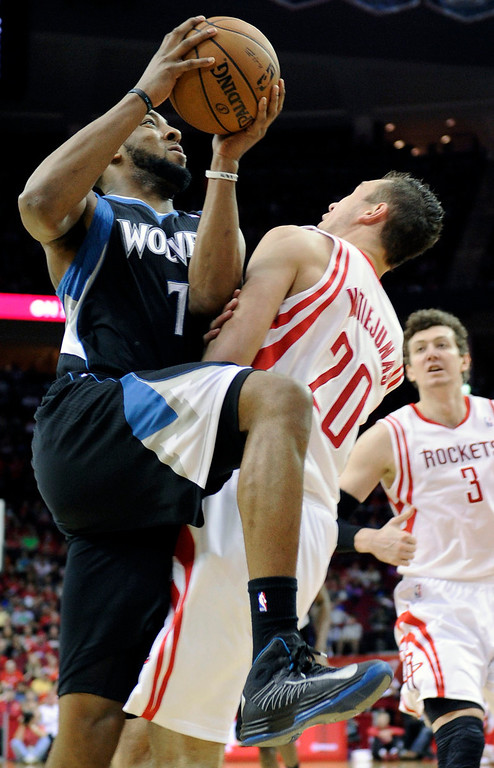 . Minnesota Timberwolves\' Derrick Williams commits an offensive foul against Houston Rockets\' Donatas Motiejunas. (AP Photo/Pat Sullivan)