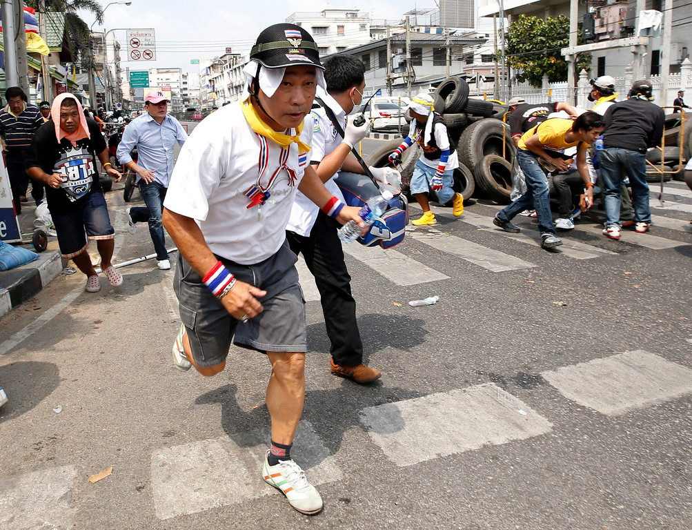 . Thai anti-government protesters flee from gunshots during clashes with anti-riot policeman at a protest site near Government House in Bangkok, Thailand, 18 February 2014. EPA/RUNGROJ YONGRIT