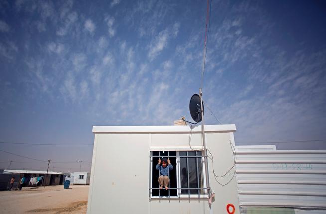 . In this Thursday, April 17, 2014 photo, a Syrian boy plays on the window of a caravan at Zaatari refugee camp, near the Syrian border in Jordan. (AP Photo/Khalil Hamra)