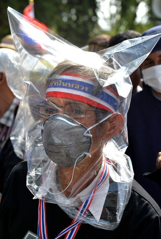 . An anti-government protestor with his face covered in a plastic bag looks on towards Government House in Bangkok on February 18, 2014.    AFP PHOTO / Manjunath  Kiran/AFP/Getty Images