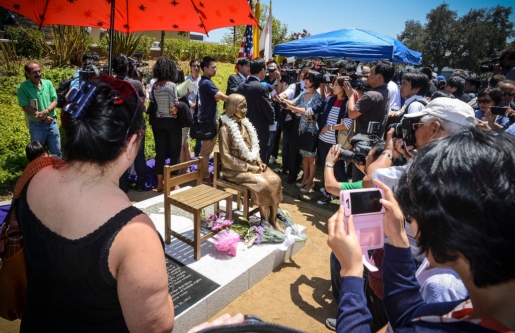 ". Crowds gather around the newly unveiled of a statue honoring the ""comfort women\"" of WWII in Glendale Tuesday.  Photo by David Crane/Staff Photographer"