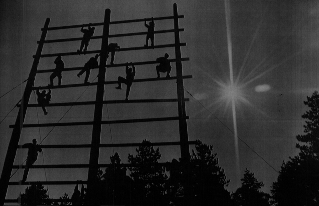 . Cadet candidates climb to the top of a confidence course obstacle as part of Basic Cadet Training in Jack\'s Valley at the Air Force Academy Friday morning. 1986. The Denver Post Library Archive
