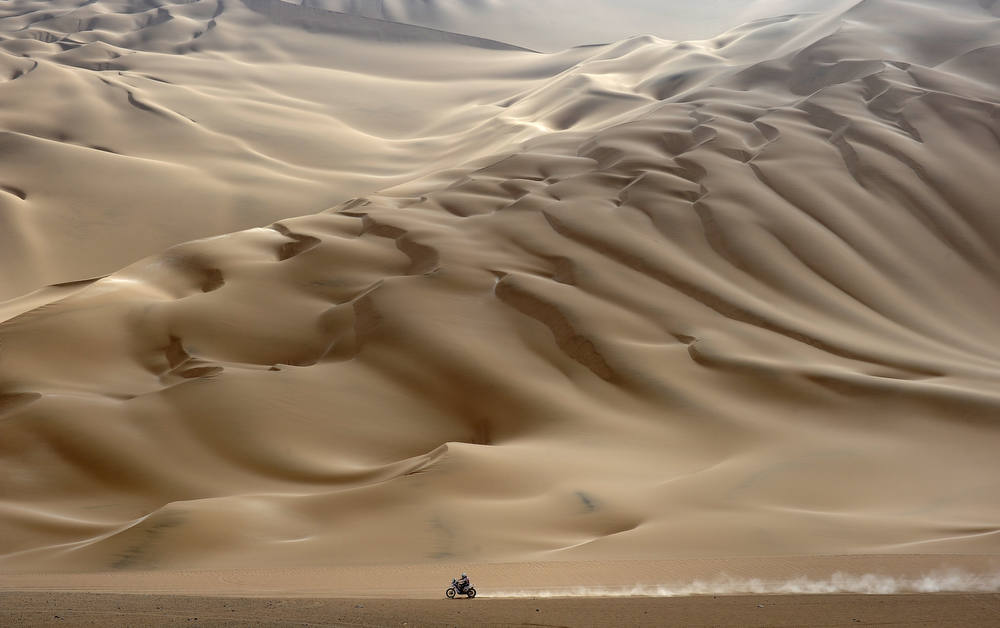 Description of . A lonesome motorcyclist rides across the desert during the stage 11 of the Dakar 2012, between Arica and Arequipa, Chile, on January 12, 2012. French Cyril Despres won stage 11.     AFP PHOTO/PHILIPPE  DESMAZES/AFP/Getty Images