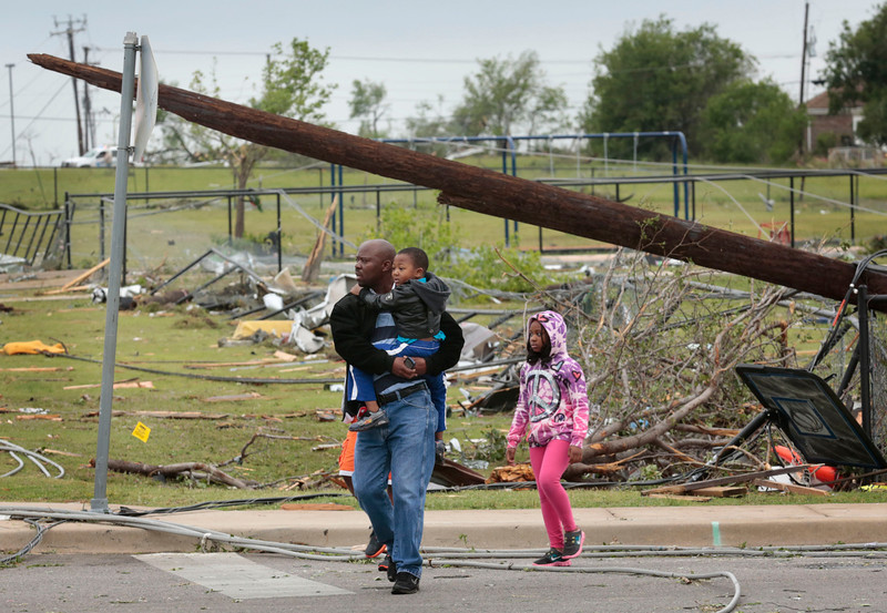 . Residents tour the damage on Thursday, May 16, 2013, after a tornado destroyed part of Cleburne, Texas Wednesday night.  A rash of tornadoes slammed into several small communities in North Texas overnight, leaving at least six people dead, dozens more injured and hundreds homeless. The violent spring storm scattered bodies, flattened homes and threw trailers onto cars.  (AP Photo/The Dallas Morning News, Michael Ainsworth)