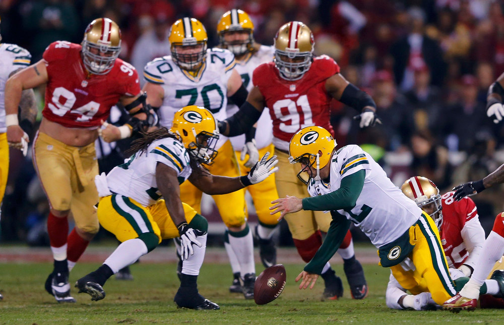 Description of . Green Bay Packers Aaron Rodgers (C) recovers his own fumble as he is tackled by San Francisco 49ers Aldon Smith (R) next to teammate DuJuan Harris (L) in the second quarter during their NFL NFC Divisional playoff football game in San Francisco, California, January 12, 2013. REUTERS/Mike Blake