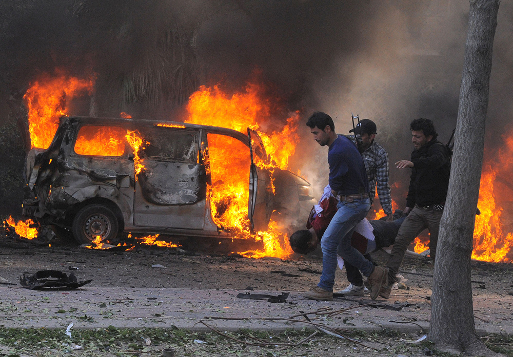 Description of . This photo released by the Syrian official news agency SANA, shows Syrian security agents carrying a body following a huge explosion that shook central Damascus, Syria, Thursday, Feb. 21, 2013. A car bomb shook central Damascus on Thursday, exploding near the headquarters of the ruling Baath party and the Russian Embassy, eyewitnesses and opposition activists said. (AP Photo/SANA)