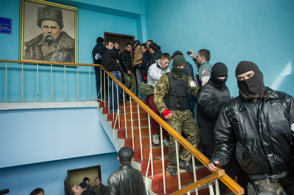 . Crimean pro-Russian self-defense forces walk through the Ukrainian navy headquarters, with a picture of 19th century Ukrainian poet and writer Taras Shevchenko, in Sevastopol, Crimea, Wednesday, March 19, 2014.  (AP Photo/Andrew Lubimov)