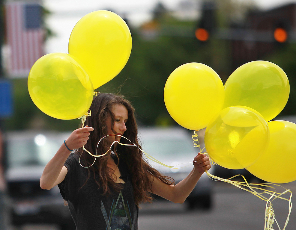 . Rachel Malone, 17, ties balloons along Main Street in Hailey, Idaho on Saturday, May 31, 2014 after the announcement that U.S. Army Sgt. Bowe Bergdahl has been released from captivity. Bergdahl, 28, had been held prisoner by the Taliban since June 30, 2009. He was handed over to U.S. special forces by the Taliban in exchange for the release of five Afghan detainees held by the United States. (AP Photo/The Times-News, Drew Nash)