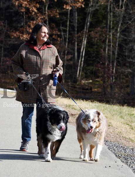 Harold Aughton/Butler Eagle: Diane Shaeffer of Middlesex Twp., a retired HR director, walks her Australian Shepherds, Jags, (left) and Bella along the lake shore at Glade Run, Mon., Nov. 18, 2019.