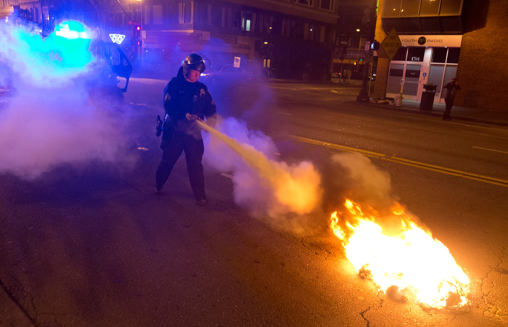 . An Oakland, Calif. police officer uses a fire extinguisher to quell the fire from a burning bag of garbage left by demonstrators during a protest of the verdict in the Trayvon Martin murder trial last Saturday in Sanford, Fla., Monday, July 15, 2013 in Oakland. (D. Ross Cameron/Bay Area News Group)