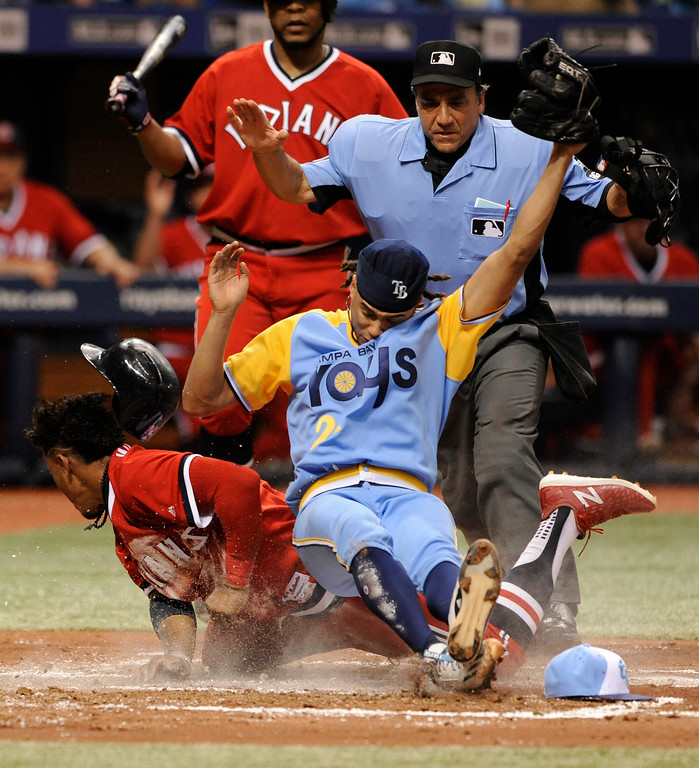 . Home plate umpire Phil Cuzzi, back right, looks on as Cleveland Indians\' Francisco Lindor, left, scores on a wild pitch from Tampa Bay Rays starter Chris Archer, covering the plate, during the third inning of a baseball game Saturday, Aug. 12, 2017, in St. Petersburg, Fla. (AP Photo/Steve Nesius)