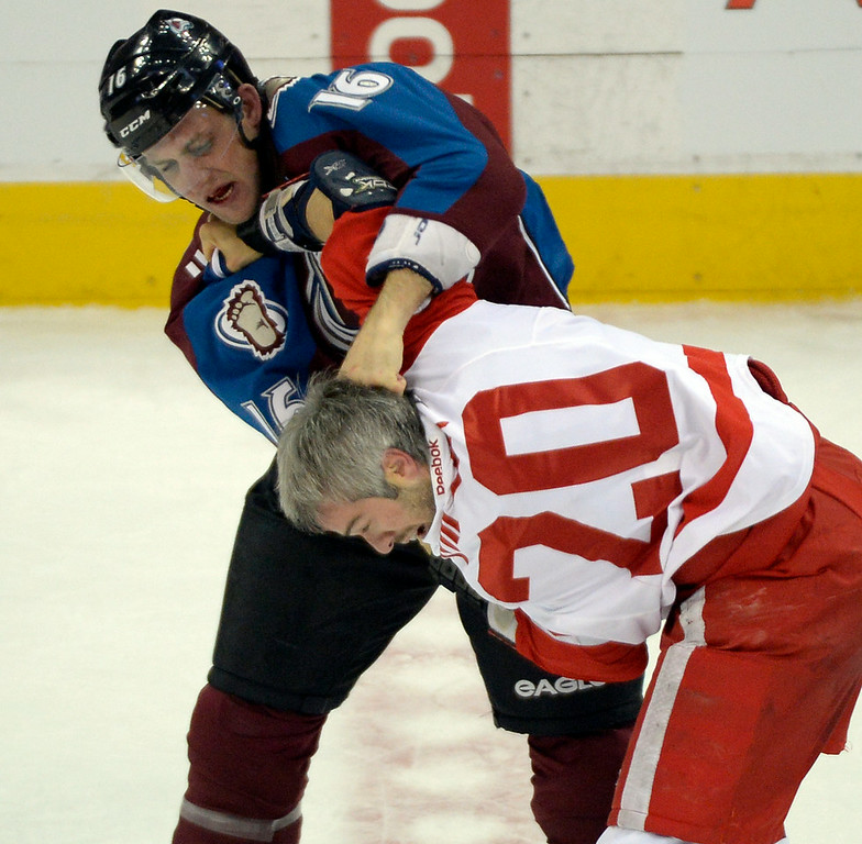 . Colorado Avalanche defenseman Cory Sarich (16) lands a shot on Detroit Red Wings left wing Drew Miller (20) during a fight in the second period  October 17, 2013 at Pepsi Center.(Photo by John Leyba/The Denver Post)