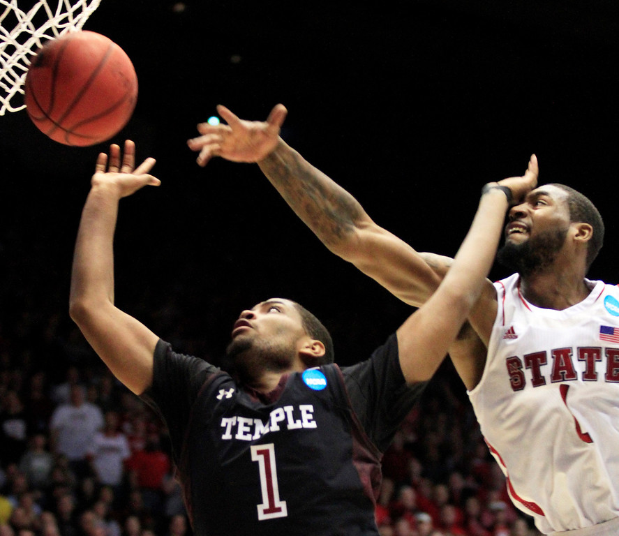 . CORRECTS BYLINE - Temple guard Khalif Wyatt, left, drives to the basket against North Carolina State forward Richard Howell in the second half of a second-round game at the NCAA college basketball tournament, Friday, March 22, 2013, in Dayton, Ohio. Wyatt led Temple to a 76-72 win with 31 points. (AP Photo/Skip Peterson)