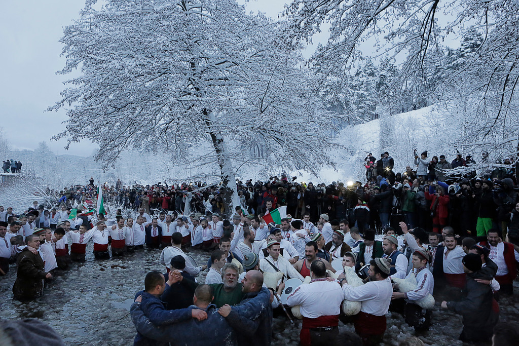 . Believers sing and dance in the icy water of the river Tundzha as they celebrate Epiphany day, a Christian festival, in the town of Kalofer, Bulgaria, Friday, Jan. 6, 2017. Traditionally, an Eastern Orthodox priest throws a cross in the river and it is believed that the one who retrieves it will be healthy through the year. In the central Bulgarian town of Kalofer, hundreds of Christians marked Epiphany by donning national costumes and wading into the frigid waters of the Tundzha river. (AP Photo/Valentina Petrova)