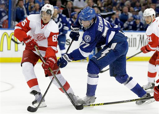 . Detroit Red Wings defenseman Danny DeKeyser (65) knocks the puck away from Tampa Bay Lightning defenseman Victor Hedman (77), of Sweden, during the second period of Game 1 of an NHL hockey first-round playoff series Thursday, April 16, 2015, in Tampa, Fla. (AP Photo/Chris O\'Meara)