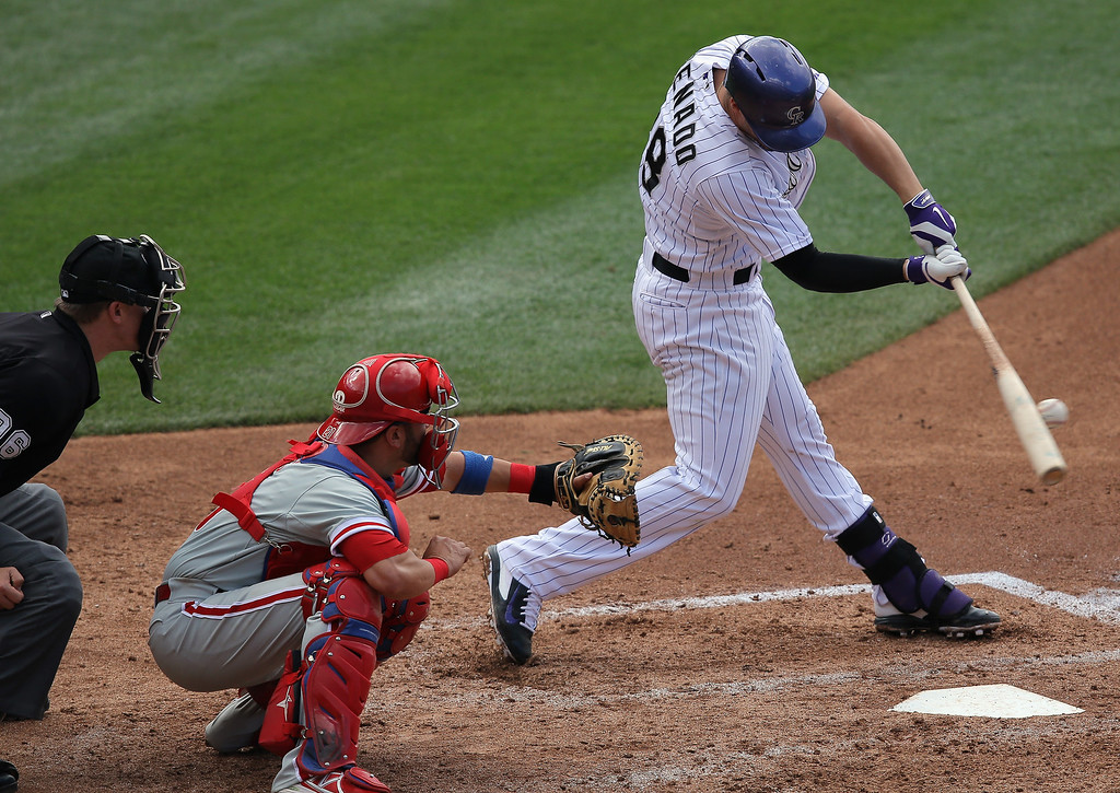 . Nolan Arenado #28 of the Colorado Rockies hits an RBI single off of Roberto Hernandez #27 of the Philadelphia Phillies to score Troy Tulowitzki #2 of the Colorado Rockies and take a 4-3 lead in the third inning at Coors Field on April 20, 2014 in Denver, Colorado.  (Photo by Doug Pensinger/Getty Images)