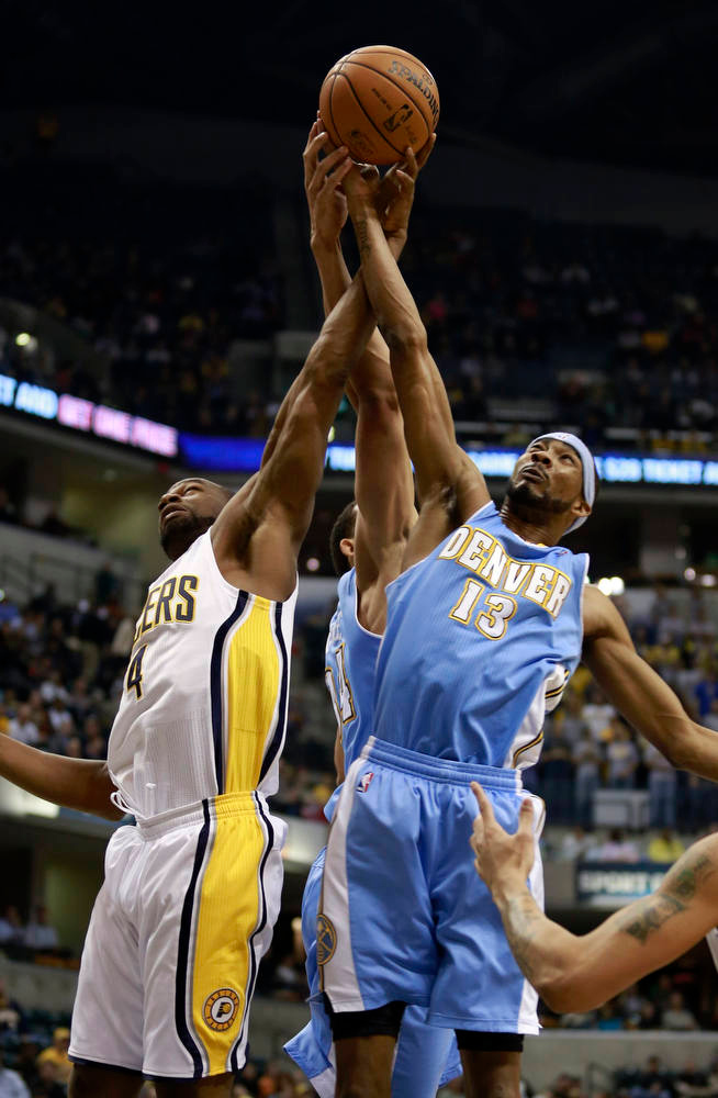 . Indiana Pacers forward Sam Young (L) and Denver Nuggets forward Corey Brewer (13) battle for a rebound during the first quarter of an NBA basketball game in Indianapolis, Indiana December 7, 2012.  REUTERS/Brent Smith