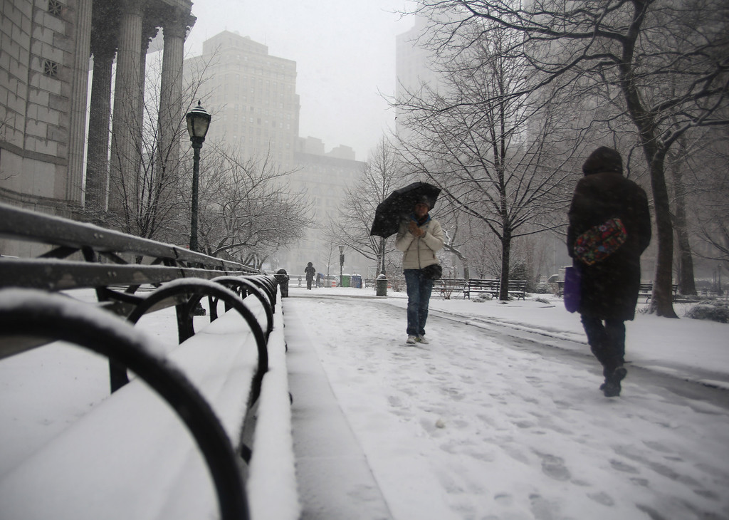 . People walk through driving snow near courthouses in lower Manhattan during a storm on Friday, March. 8 2013, in New York. (AP Photo/Peter Morgan)