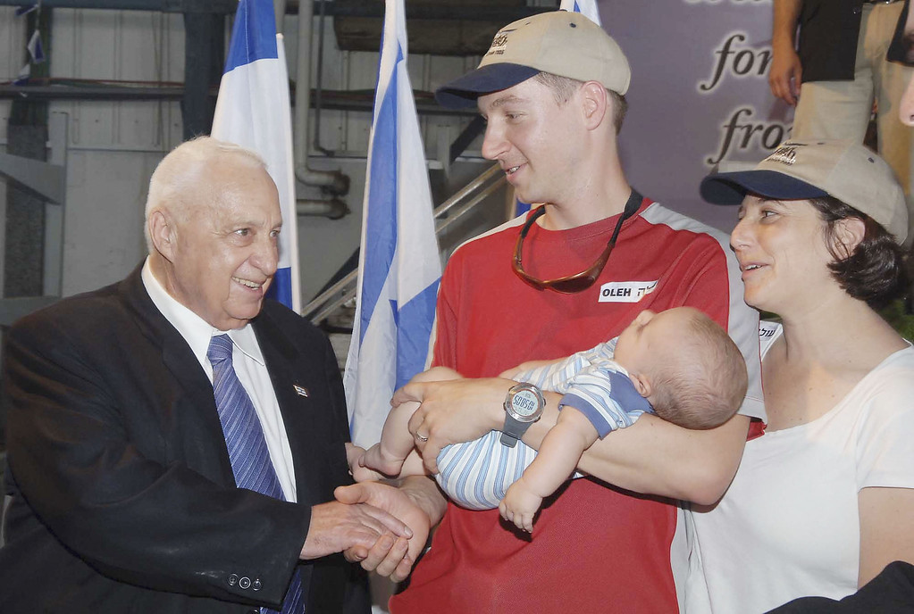 . In this handout picture Prime Minister of Israel Ariel Sharon (C) poses with new immigrants from North America to Israel at Ben Gurion airport on July 13, 2005 in Tel Aviv, Israel. Sharon ordered troops to tackle and crush Islamic Jihad and promised a swift retaliation for the suicide bombing at a shopping mall that killed 3 on July 12. (Photo by Moshe Milner/GPO via Getty Images)