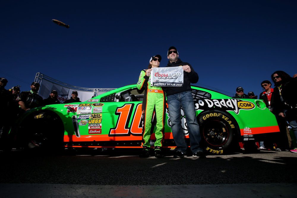 Description of . Danica Patrick, driver of the #10 GoDaddy.com Chevrolet, poses with team owner Tony Stewart holding the Coors Light Pole Award after qualifying for the NASCAR Sprint Cup Series Daytona 500 at Daytona International Speedway on February 17, 2013 in Daytona Beach, Florida.  (Photo by Jonathan Ferrey/Getty Images)