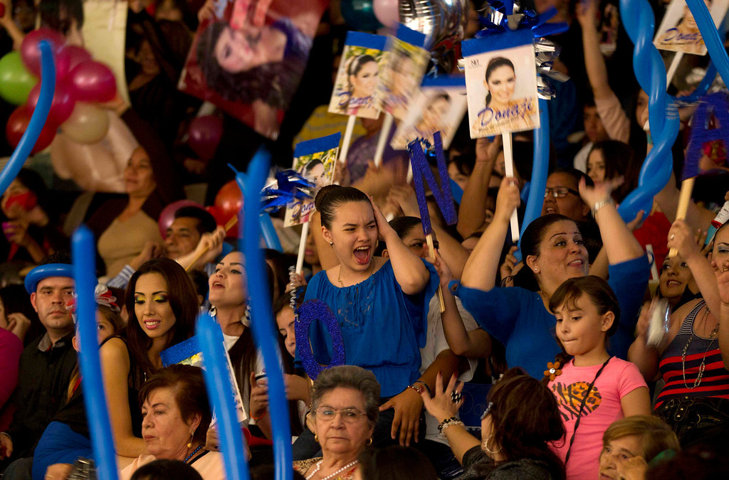 ". In this Jan. 26, 2013 photo, supporters of beauty contestant Donaji Lopez cheer for her at the ""Guamuchil Carnival Queen 2013\"" beauty pageant in Guamuchil, Sinaloa state, Mexico. Residents packed the local theater filled with banners and posters advertising the queens and filled the aisles and stairways with extra chairs after the seats filled. (AP Photo/Eduardo Verdugo)"