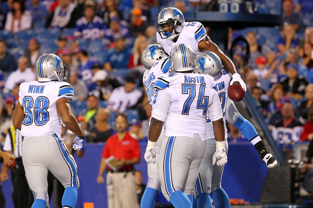 . Detroit Lions wide receiver Jeremy Ross, top, is congratulated by teammates after scoring a touchdown on a pass from quarterback Kellen Moore during the first half of a preseason NFL football game against the Buffalo Bills, Thursday, Aug. 28, 2014, in Orchard Park, N.Y. (AP Photo/Bill Wippert)