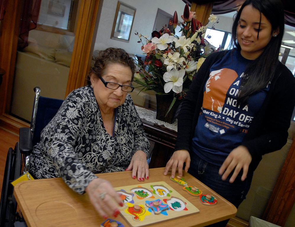 . University of Texas at Brownsville student Cinthia Baleon volunteers with Ebony Lake resident Beatrice Dominguez on Monday, Jan. 21, 2013 as a day of service to honor Martin Luther King Jr. in Brownsville, Texas. (AP Photo/The Brownsville Herald, Brad Doherty)