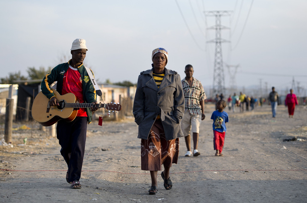 . A man with a guitar walks on July 9, 2013 in the Nkaneng shantytown next to the platinum mine, run by British company Lonmin, in Marikana. On August 16, 2012, police at the Marikana mine open fire on striking workers, killing 34 and injuring 78, during a strike was for better wages and living conditions. Miners still live in dire conditions despite a small wage increase.  ODD ANDERSEN/AFP/Getty Images
