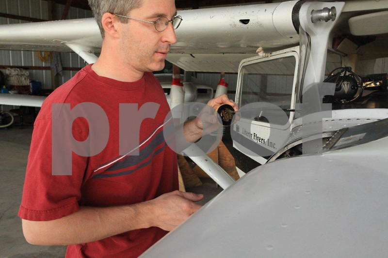 Young civilian pilot performing his pre-flight on a Cessna by chekcing the engine oil.
