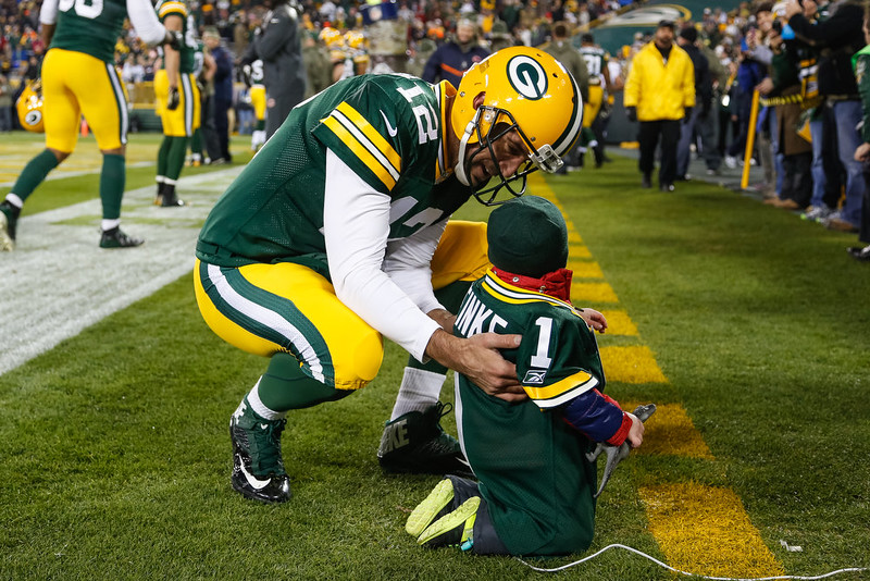 """. Quarterback Aaron Rodgers #12 of the Green Bay Packers visits with \""""Make-A-Wish\"""" foundation child, Kellan Meinke, prior to the NFL game against the Chicago Bears at Lambeau Field on November 09, 2014 in Green Bay, Wisconsin.  (Photo Tom Lynn /Getty Images)"""