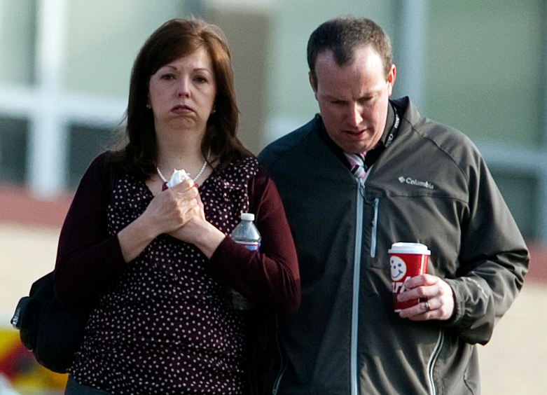 Description of . A man and woman walk away from Franklin Regional High School after more then a dozen students were stabbed by a knife wielding suspect at the school on Wednesday, April 9, 2014, in Murrysville, Pa., near Pittsburgh. The suspect, a male student, was taken into custody and is being questioned. (AP Photo/Tribune Review, Brian F. Henry)